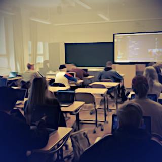 Luokkahuone, oppilaita pulpeteissa kannettavien tietokoneiden kanssa. valkokankaalla heijastettuna näkymä oppilaidenkin ruuduilla käynnissä olevasta Discord-keskustelusta.